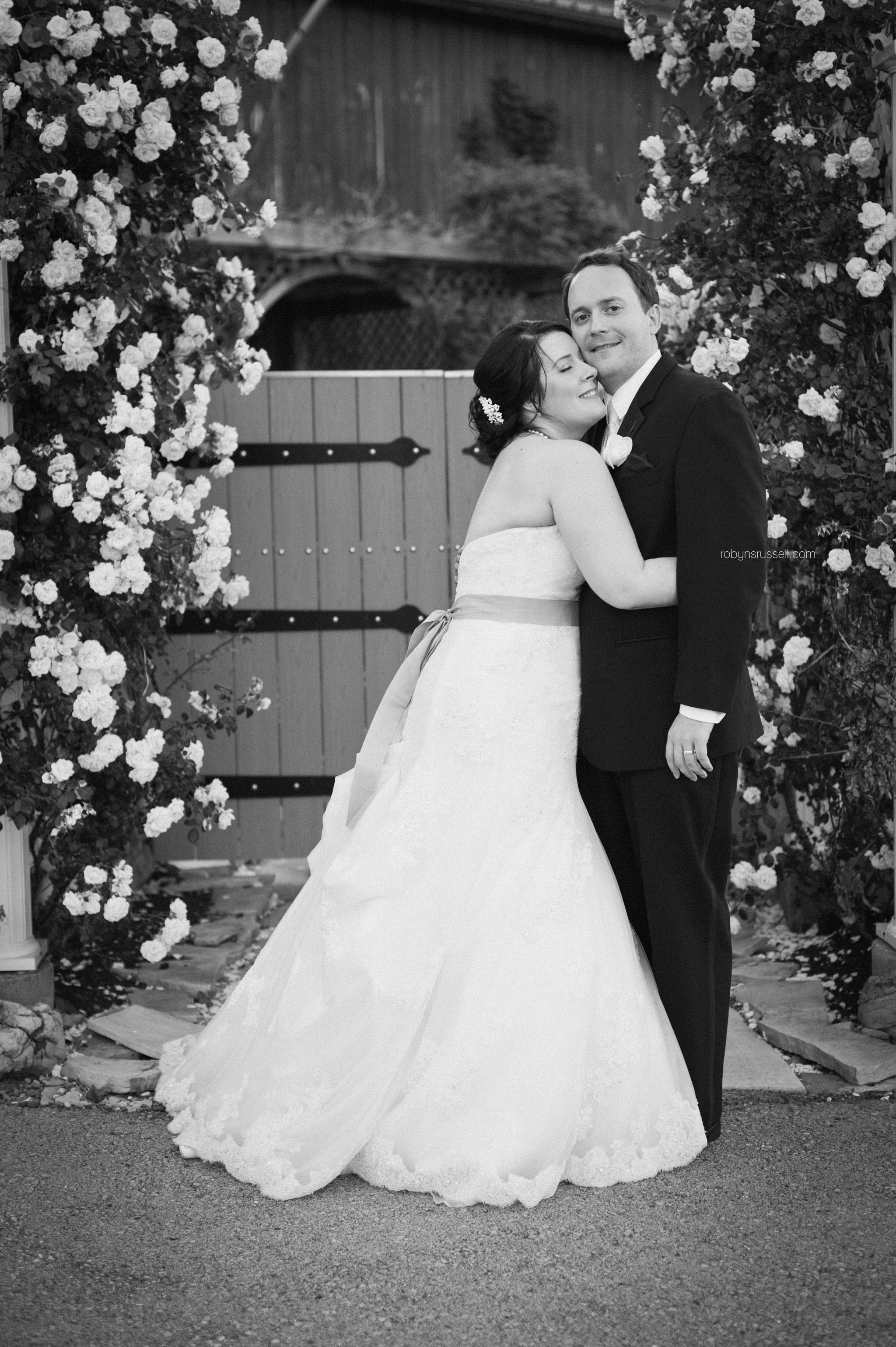 39-bride-and-groom-under-flower-arch.jpg