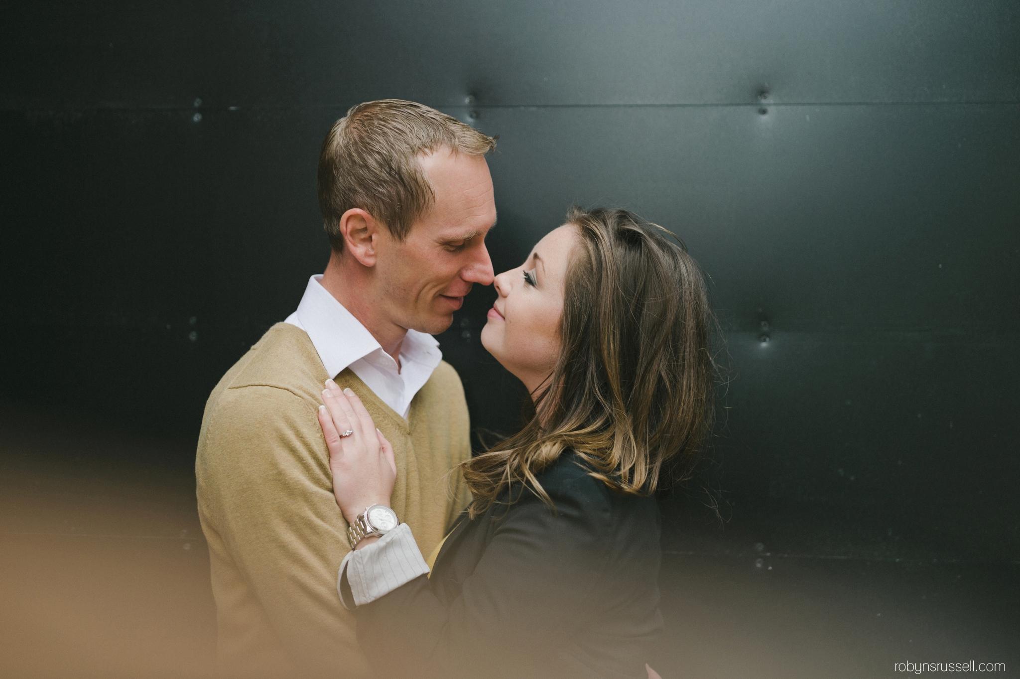 18-engaged-couple-sneaking-kiss-in-village-square-burlington.jpg