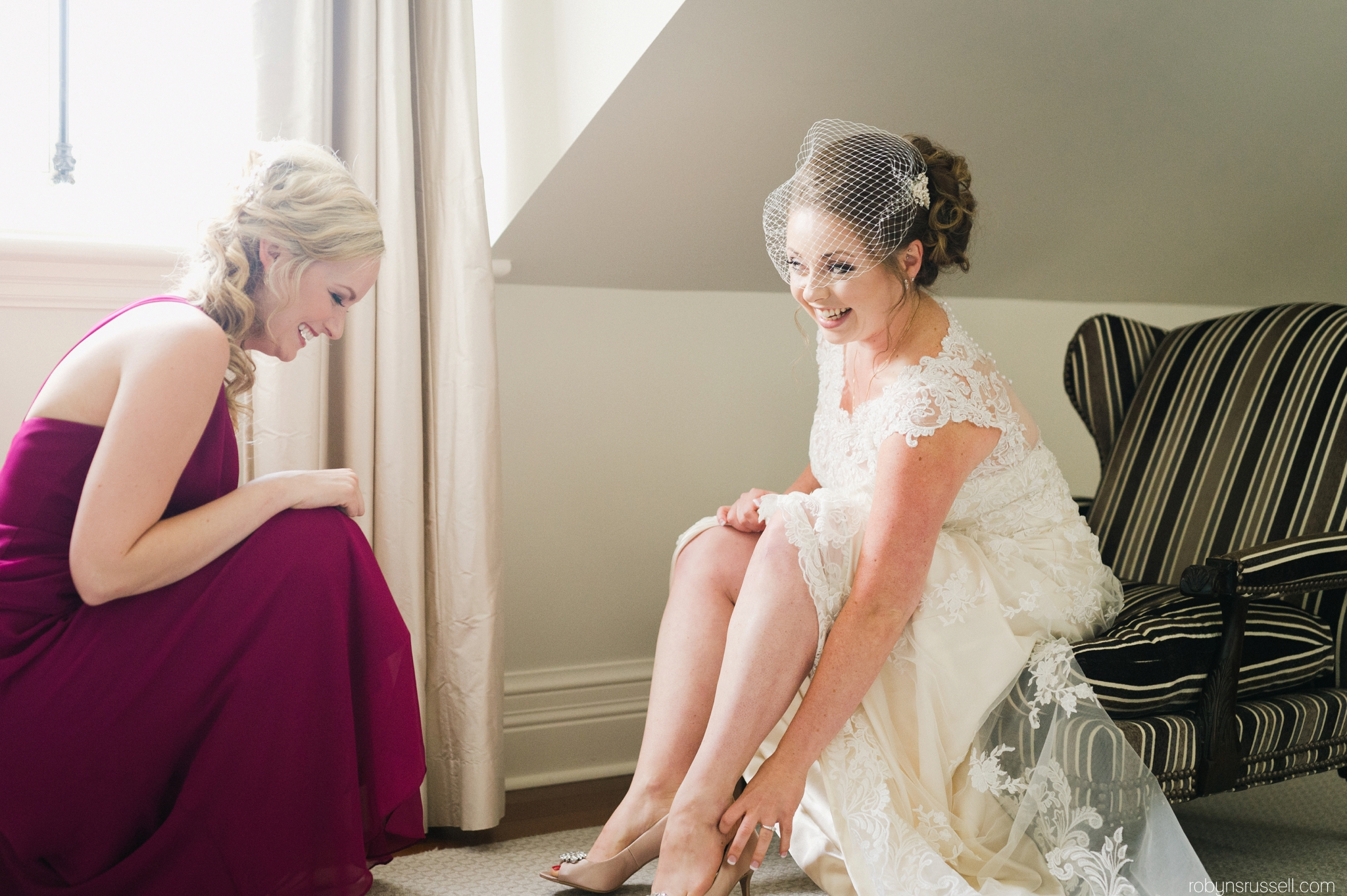 17-bride-getting-shoes-on-with-bridesmaid.jpg